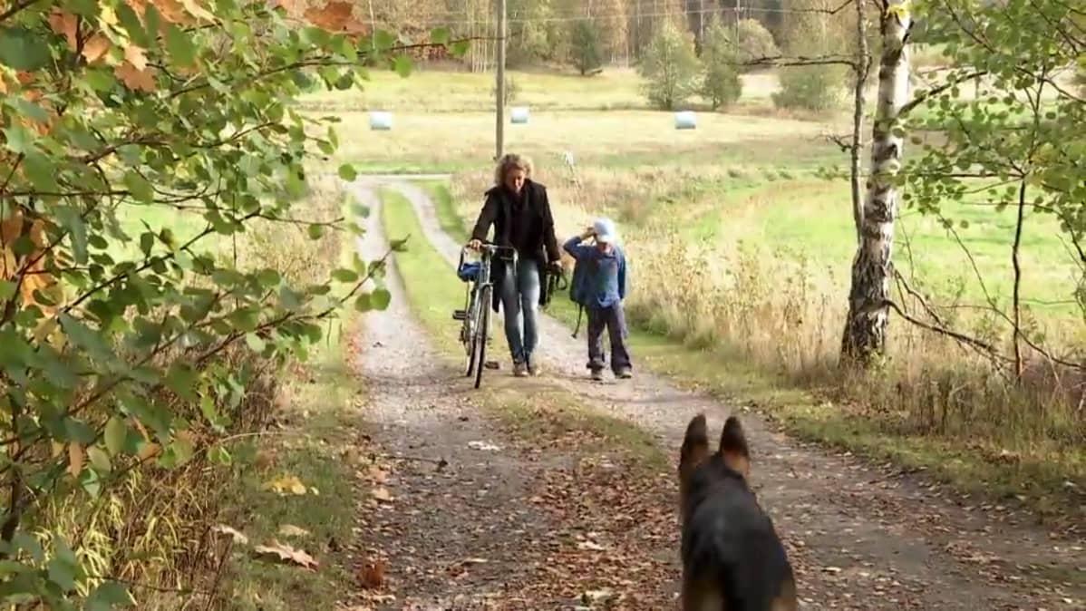 En mamma med sitt barn kommer gående, mamma leder en cykel.