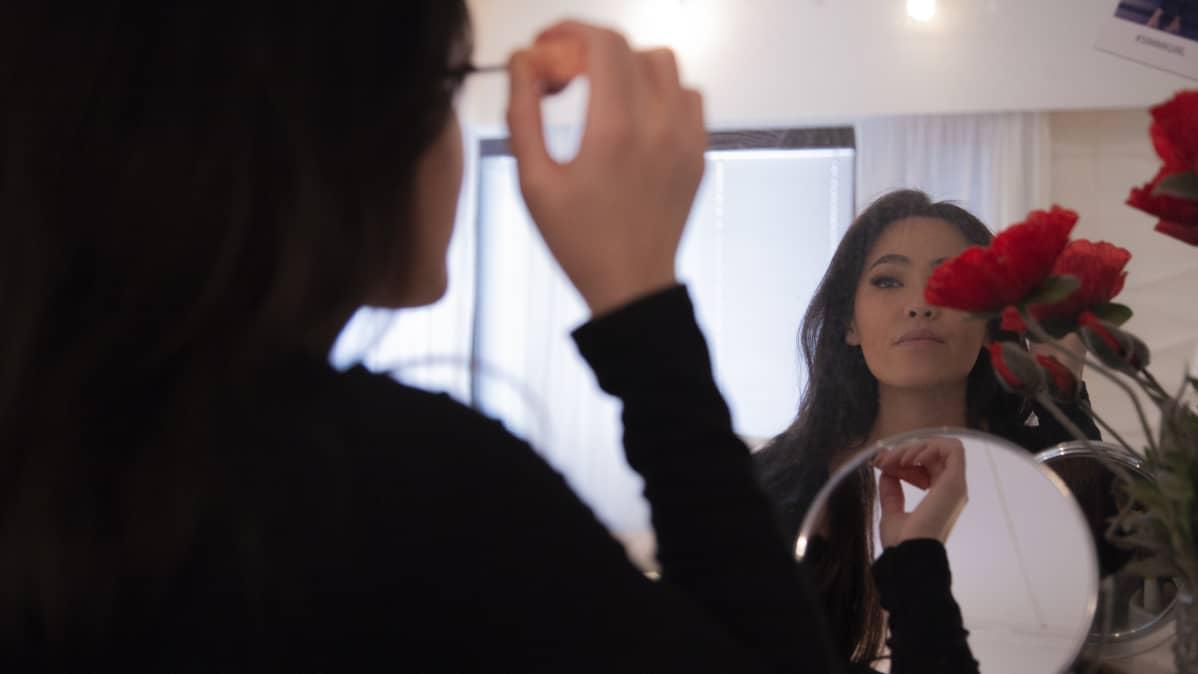 Ninni Nguyen applicerar smink hemma vid spegeln.