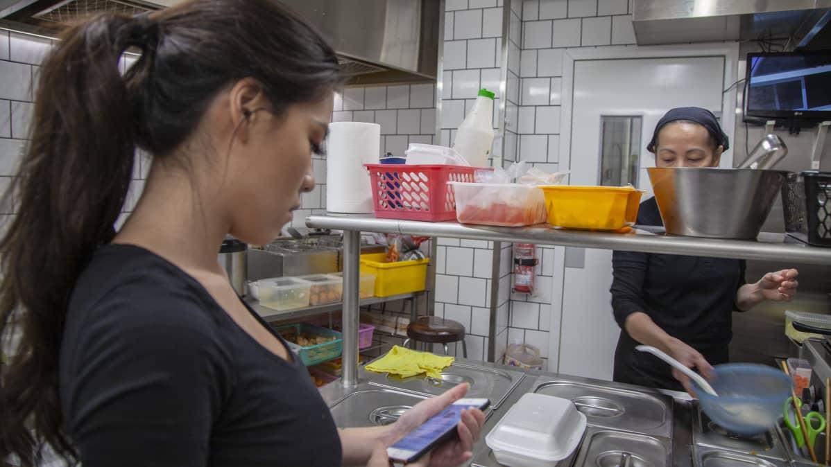 Ninni Nguyen ser på sin smarttelefon medan hon står i köket i föräldrarnas vietnamesiska restaurang.