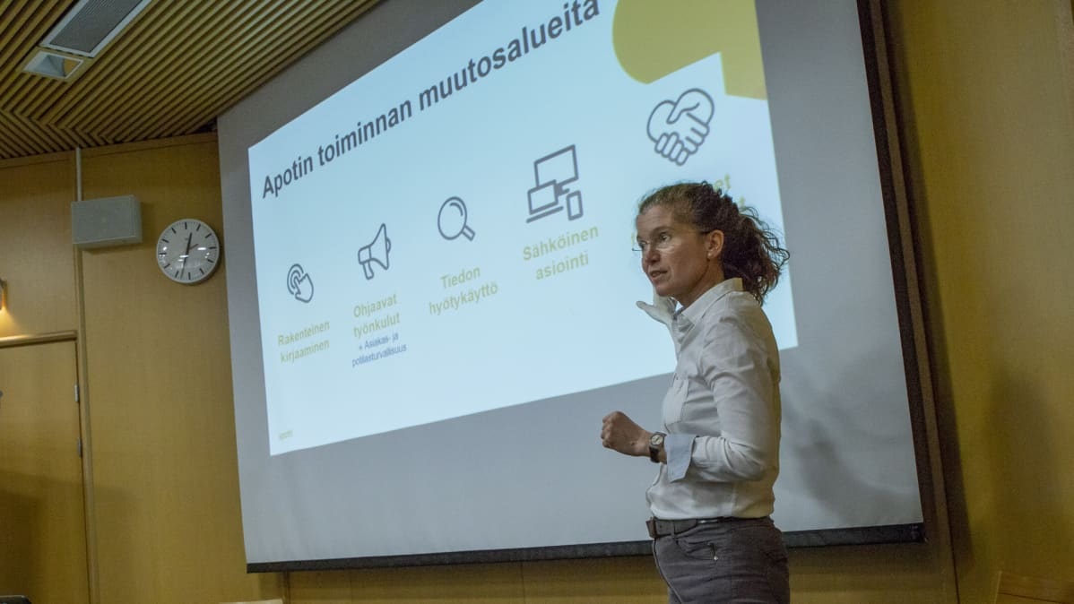 En kvinna, Piia Vuorela, står och pekar mot en powerpoint presentation om den nya patientinformationssystemet Apotti.