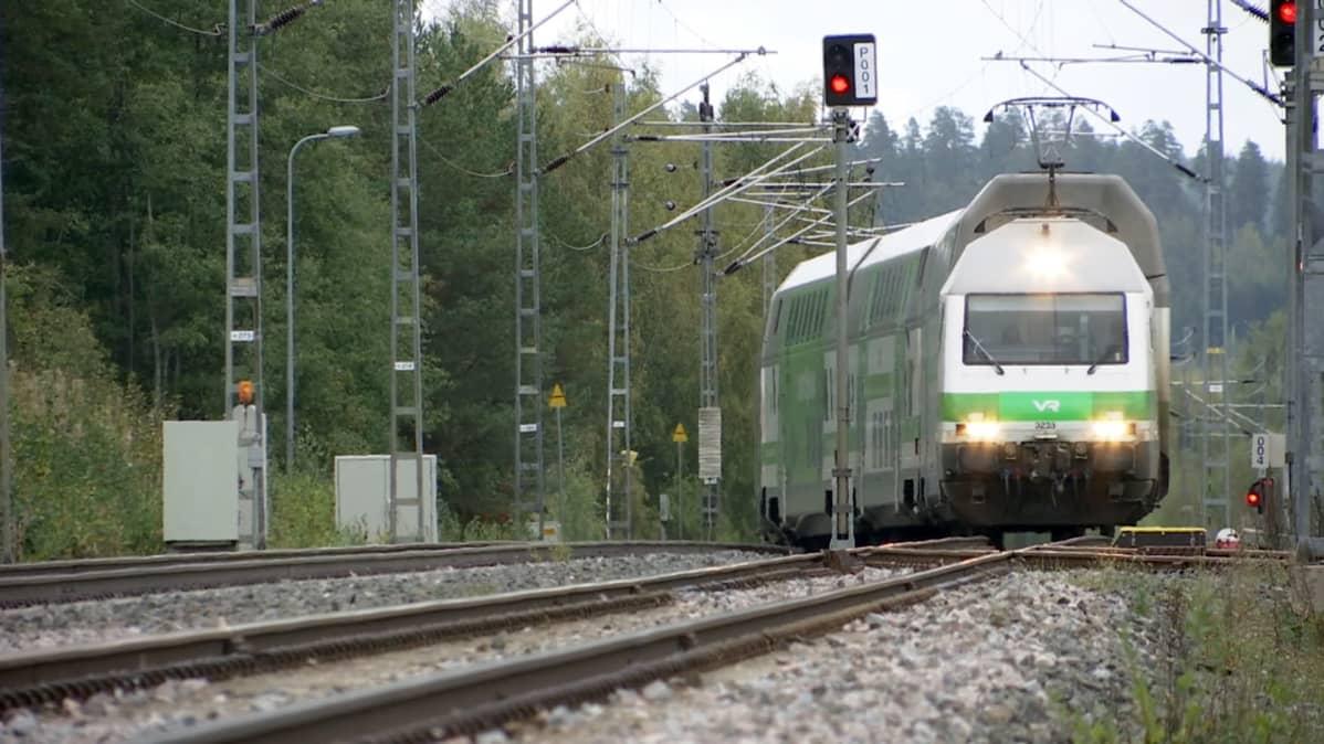 Juna lähestyy rautatietä pitkin.