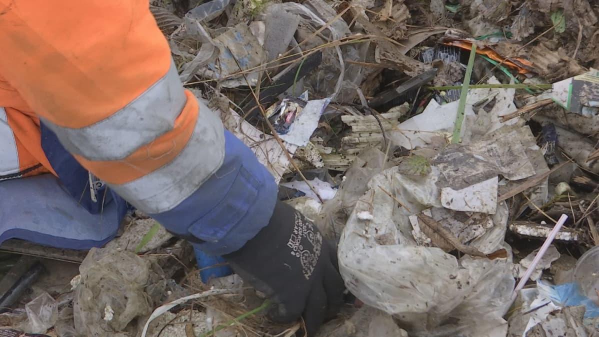 Mies tutkii jätekasaa ja nostelee muovinpalasia.