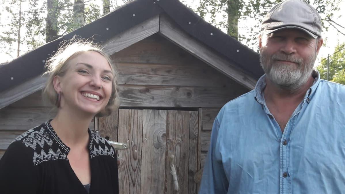 Onnen Maan ohjaaja Kirsikka Leino ja käsikirjoittaja Markku Pölönen hymyilevät puisen aitan edessä.