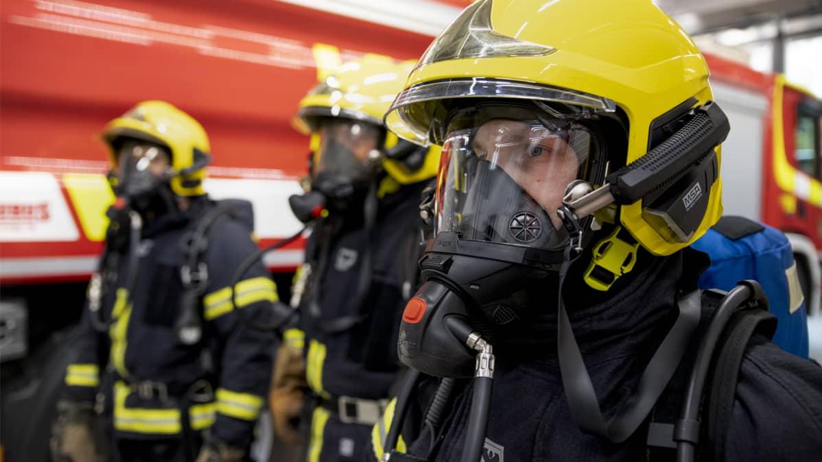 Palomiehet Hannu Kokkonen (vas,), Sami Sällinen ja Pekka Kolehmainen päällään savusukeltamisessa käytettävät paineilmalaitteet.