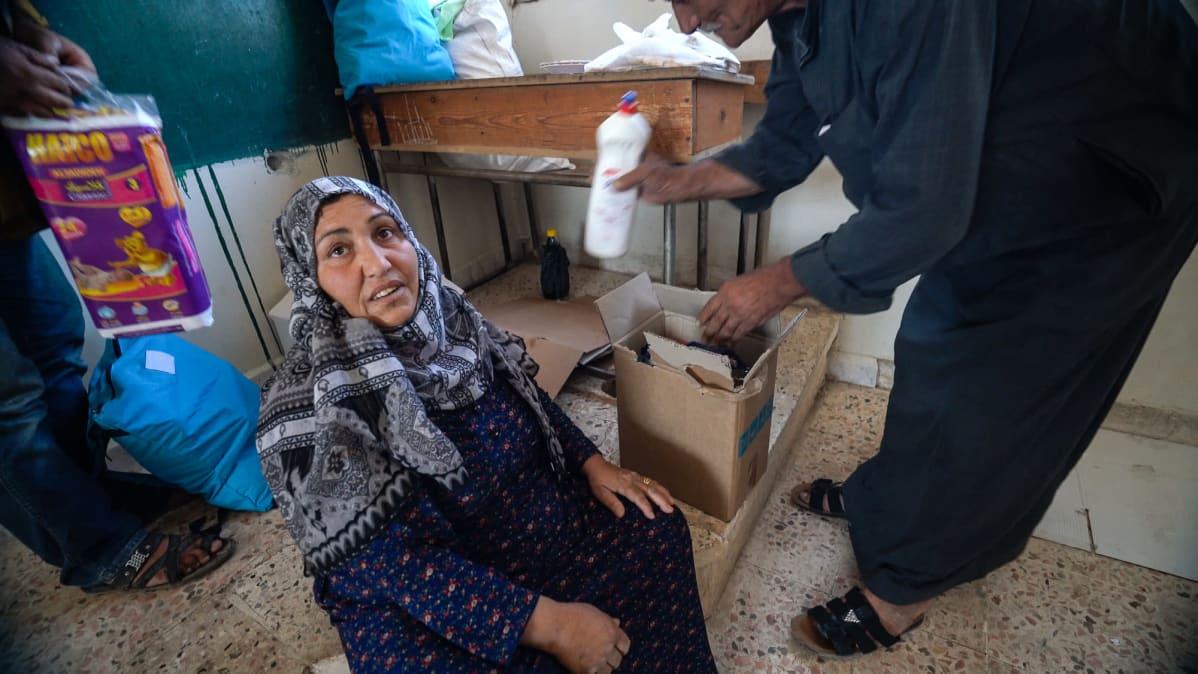 """UNICEF:in paikallinen osasto tuo humanitaarista apua kouluun. Monet saavat vain pesuaineita, joista ei ole iloa kodittomille. """"Tarvitsemme ruokaa"""", sanoo nainen."""