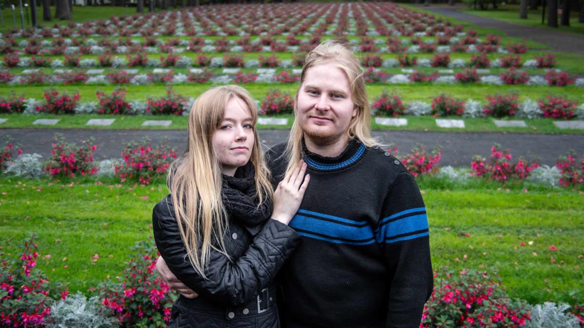 Äärikansallismielinen pariskunta Venla ja Miska Kangasniemi seisovat hautausmaalla ja hymyilevät kameralle.