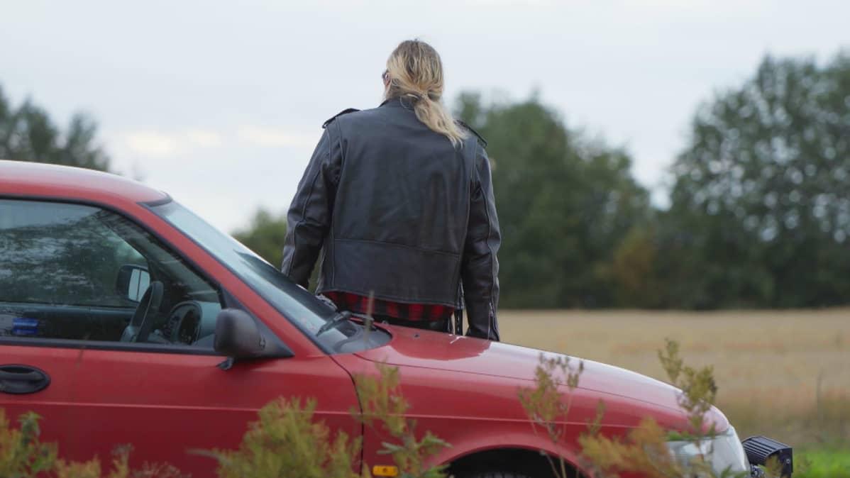 Rasmus istuu selkä kameraa kohti autonsa konepellillä ja katselee pohjalaista peltomaisemaa.