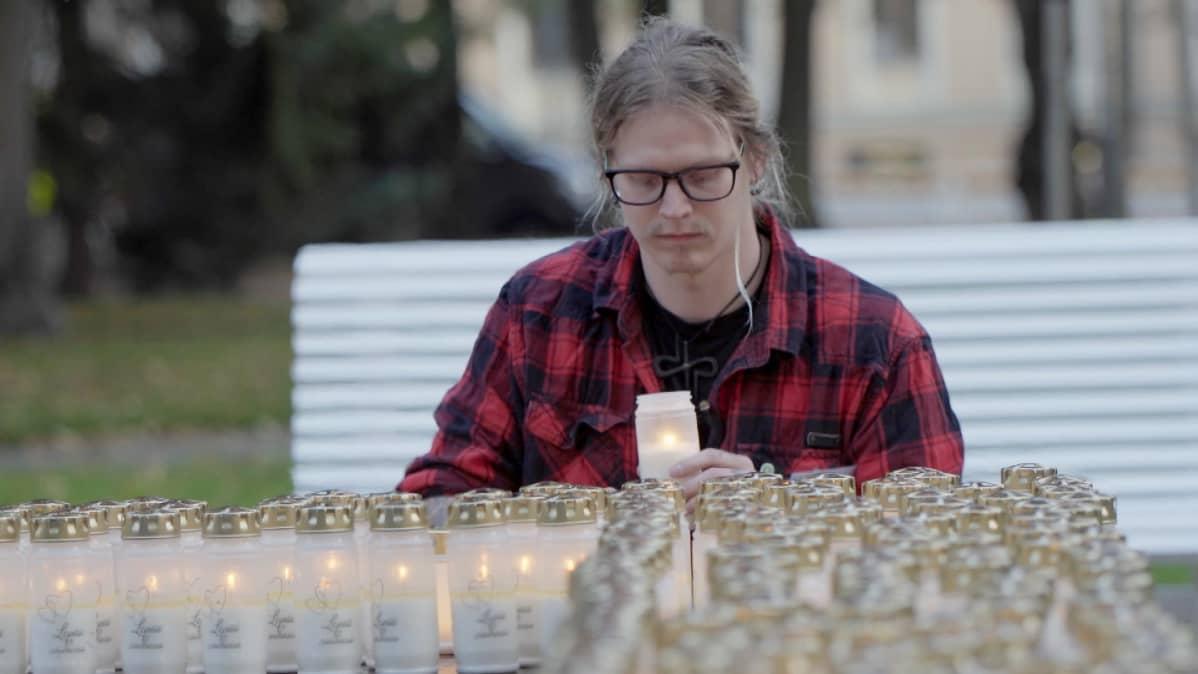 Rasmus sytyttää kynttilän itsemurhan tehneiden muistolle.