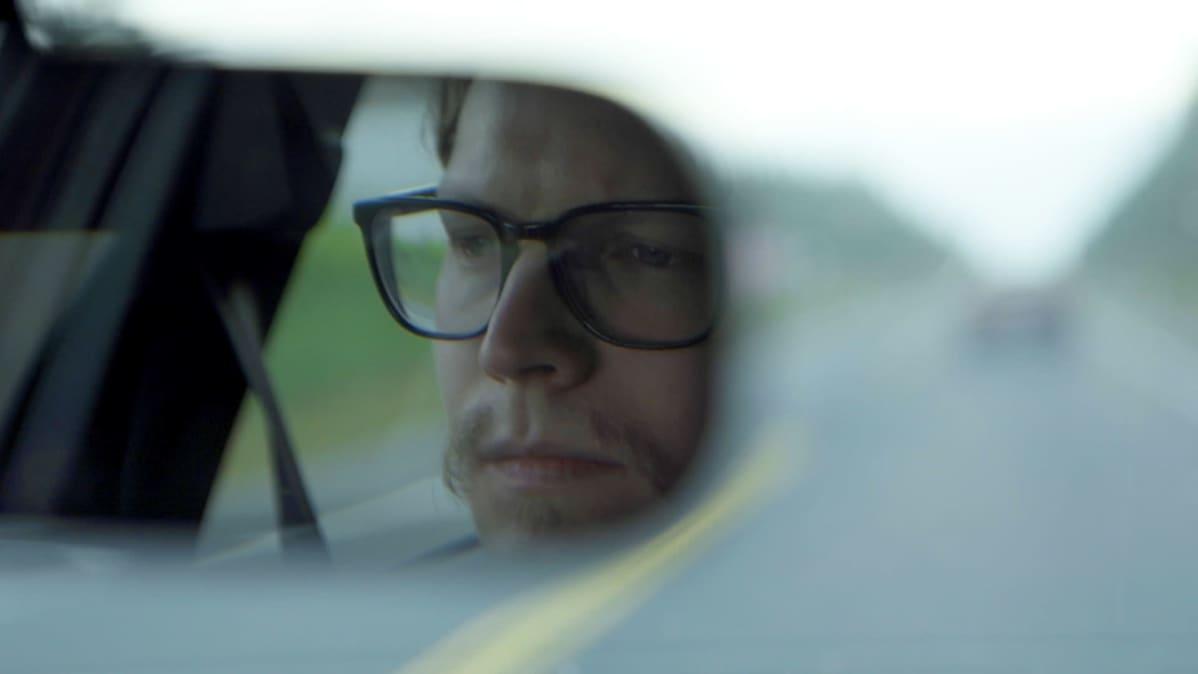 Rasmus ajaa autoa. Näkymä peruutuspeilistä Rasmuksen kasvoihin.