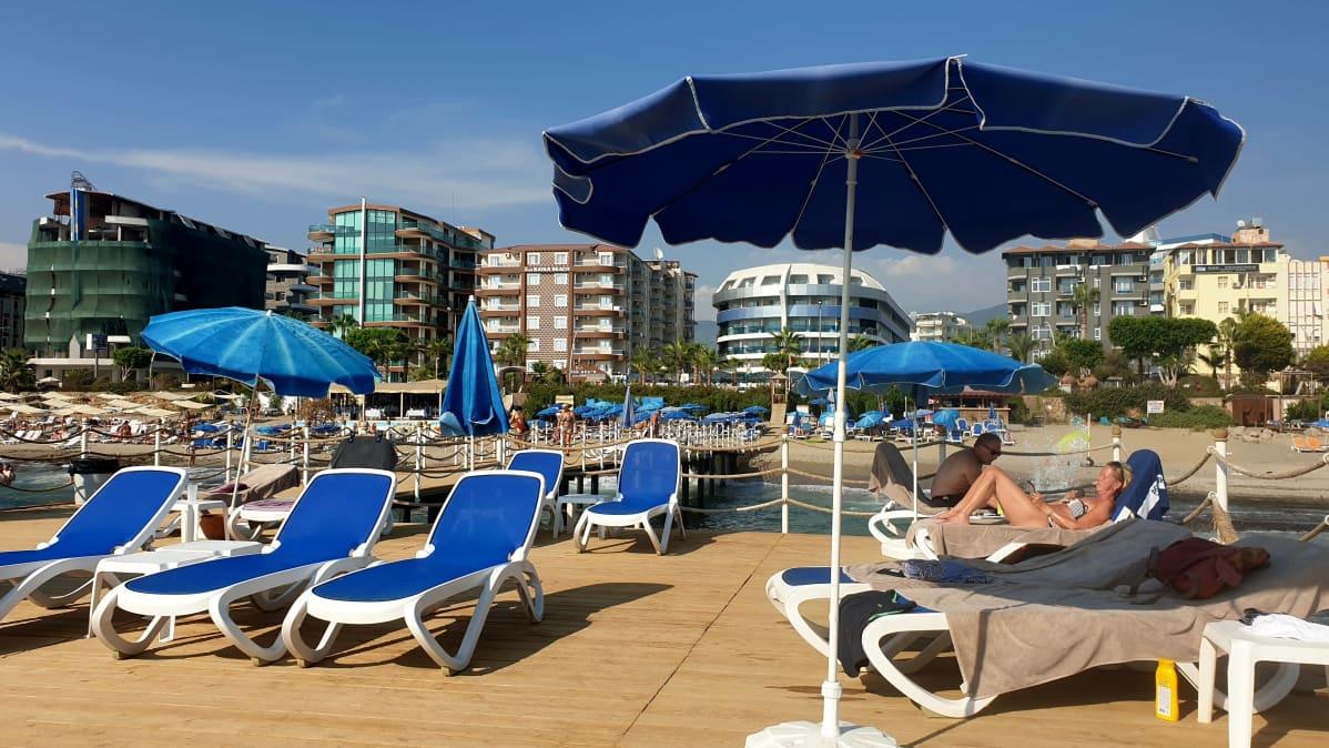 Matkailijoita Alanyassa aurinkovarjon alla rannalla