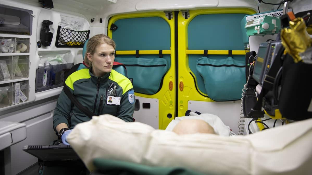 Päivystävä ensihoitaja seuraa potilaan kuntoa ambulanssin kyydissä.