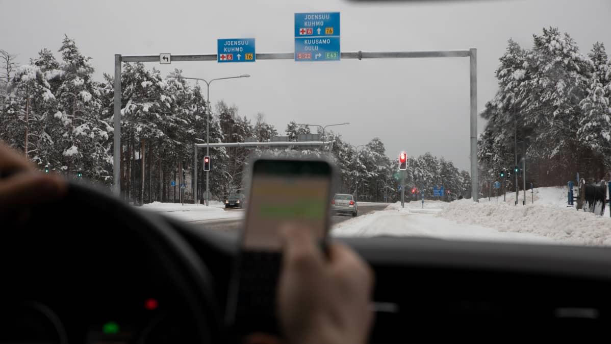 Mies räplää matkapuhelinta ajaessa autoa.