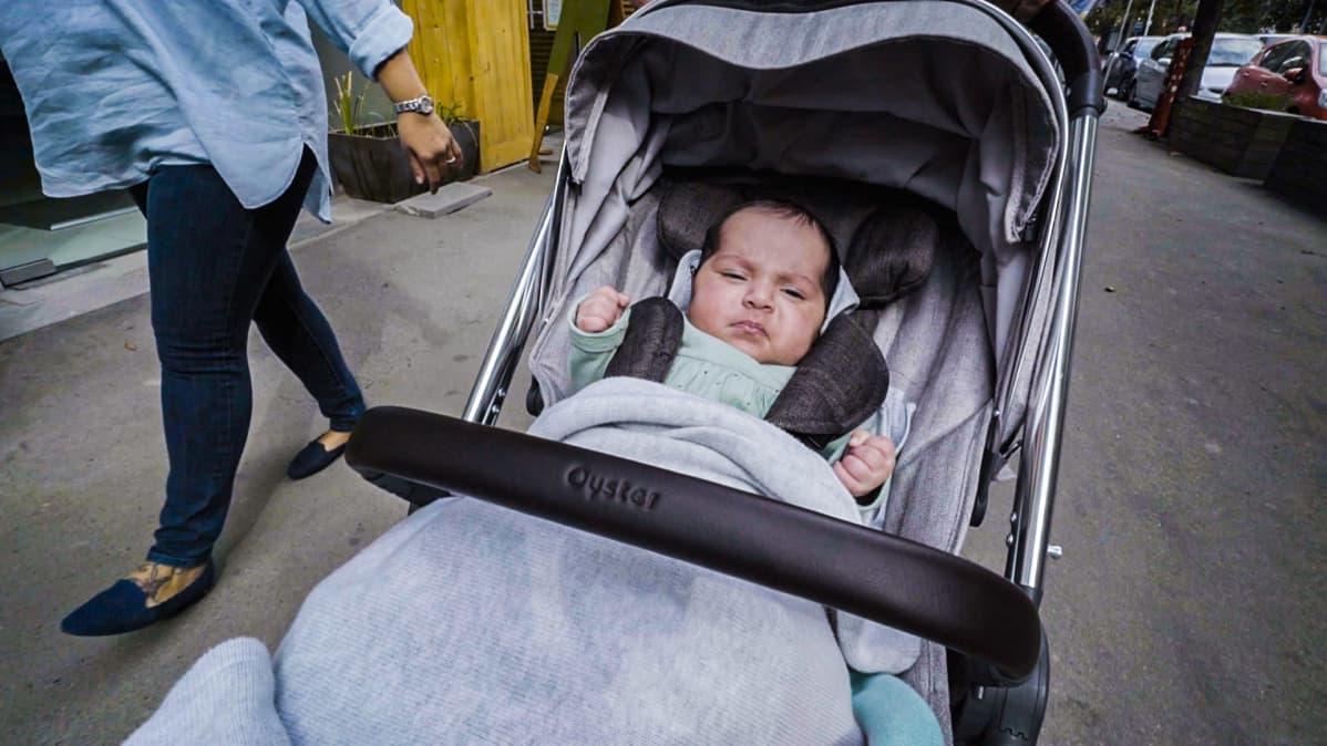 Vauvaa työnnetään lastenvaunuissa kadulla.