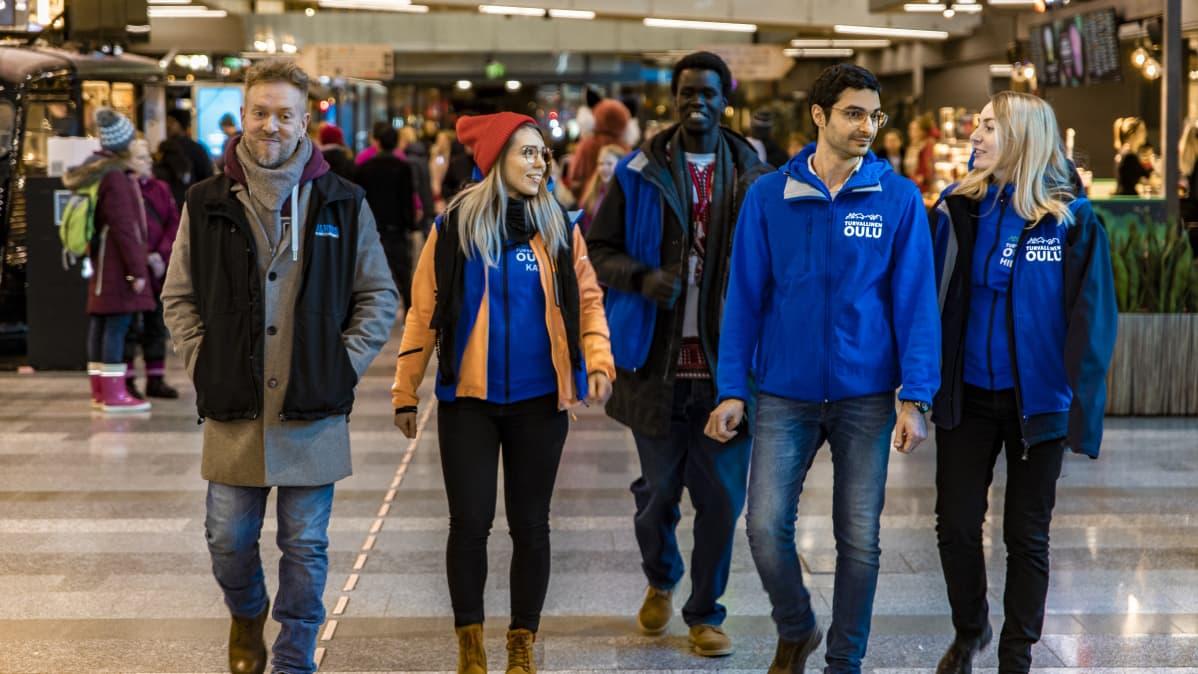 Walkersissa toimiva nuorisotyöntekijä Perttu Kemppainen ja muut Walkersin työntekijät kävelevät kauppakeskus Valkean käytävää