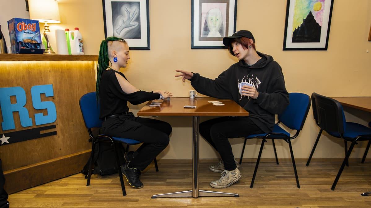 Milka Luosujärvi ja Leevi Arponen pelaavat korttipeliä Oulun Walkersissa