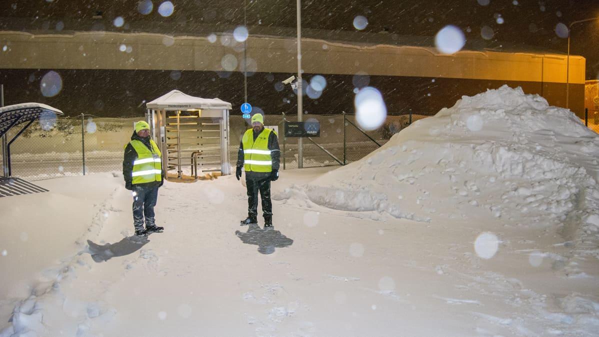 Kaksi henkilöä seisoo lumisen portin edustalla heijastinliivit päällä.