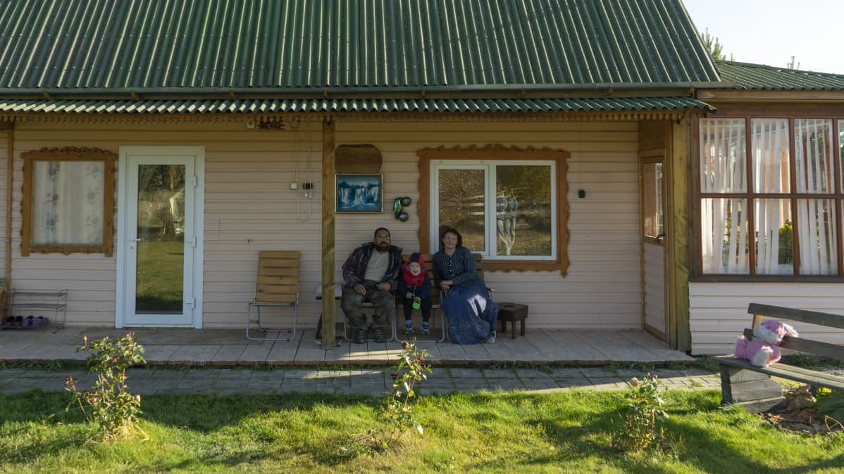Perhe istuu talon kuistilla.