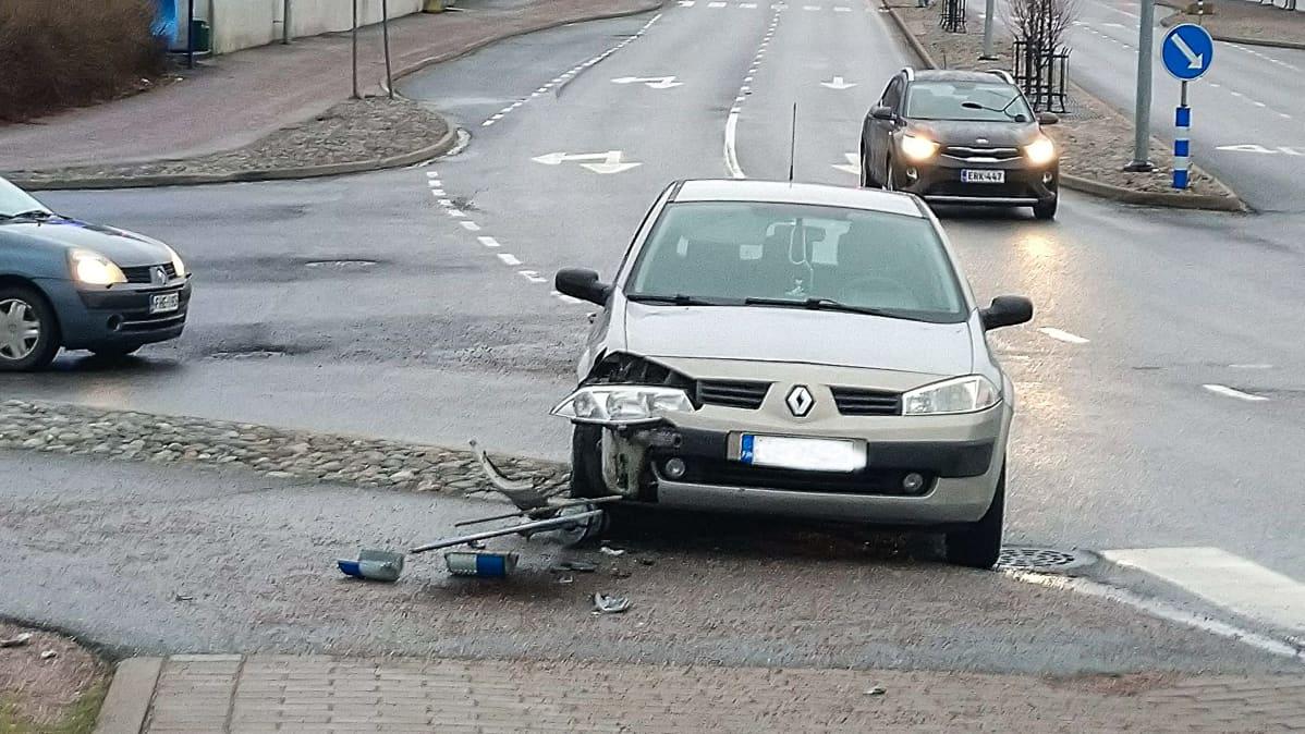 Auto kolaroinut liikennemerkin kanssa
