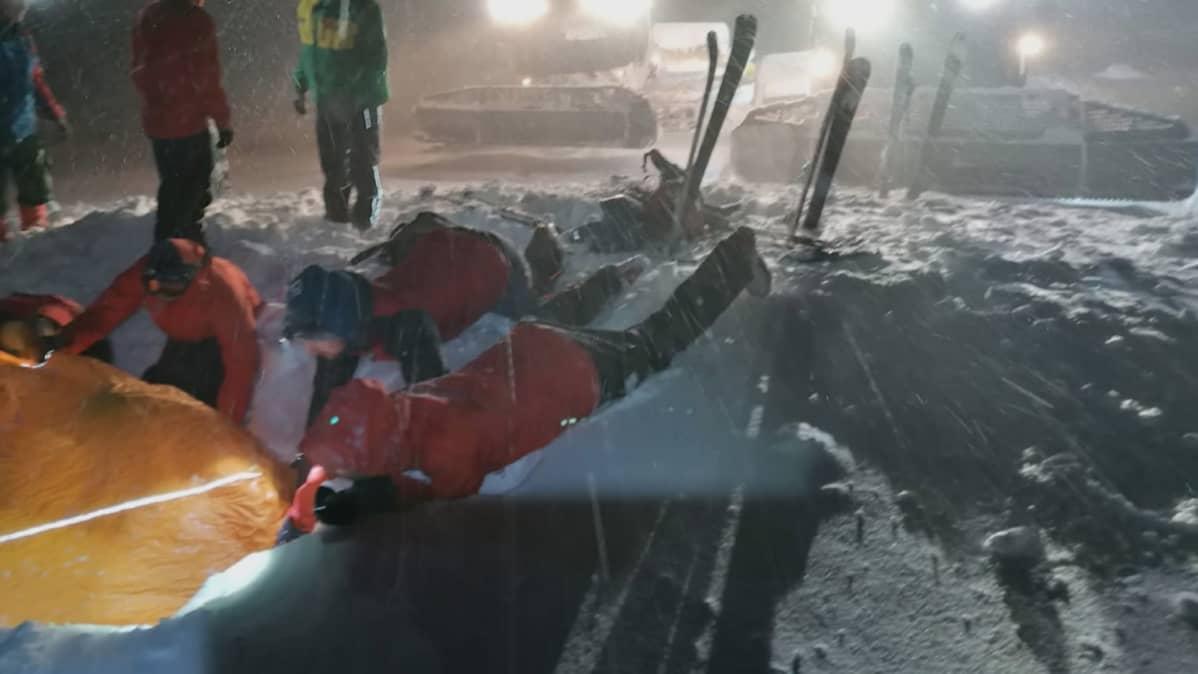 Avustustyöntekijät auttoivat lumen alle jäänyttä laskettelijaa Styriassa Itävallassa.