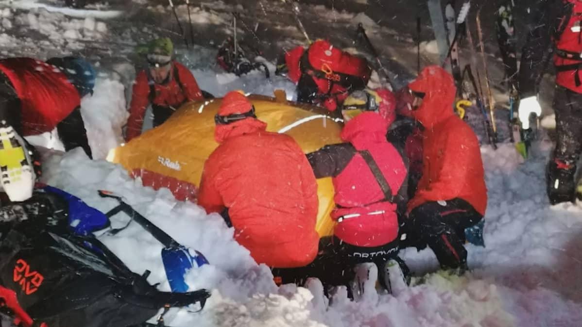 Avustustyöntekijät auttoivat lumen alle jäänyttä laskettelijaa joulupäivänä Itävallassa.
