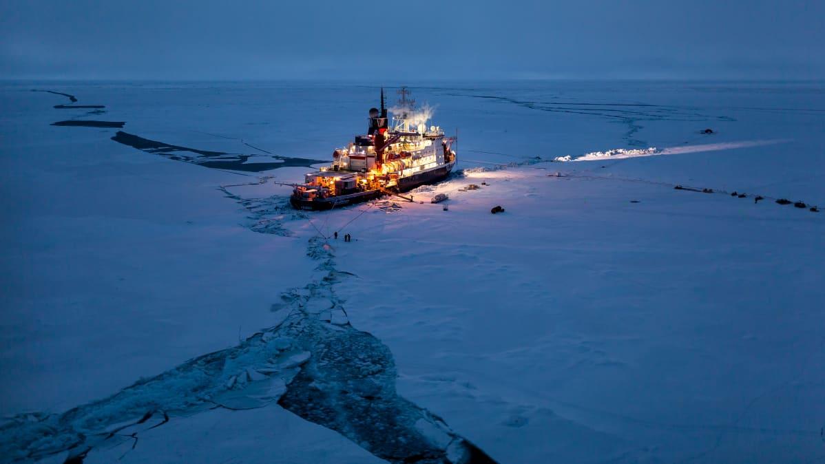 Kirkkaasti valaistu tutkimusalus tummenevalla jäisellä merellä, jossa kelluu jäälauttoja.
