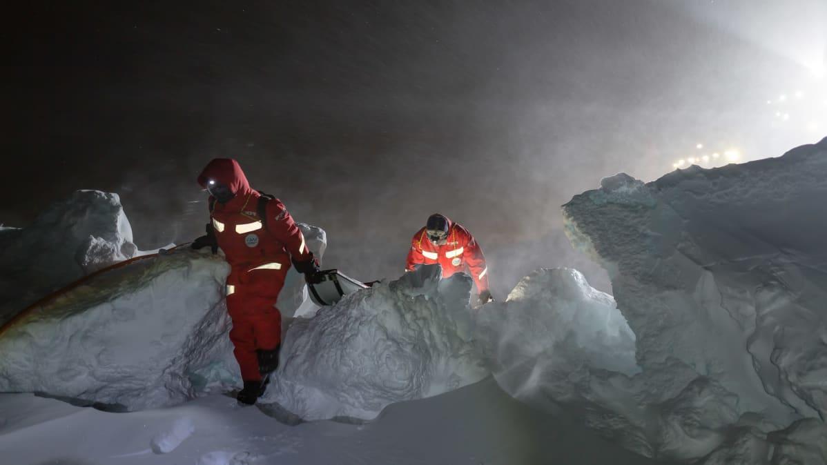 Kaksi tutkijaa kiipeä jäävallin ylitse.