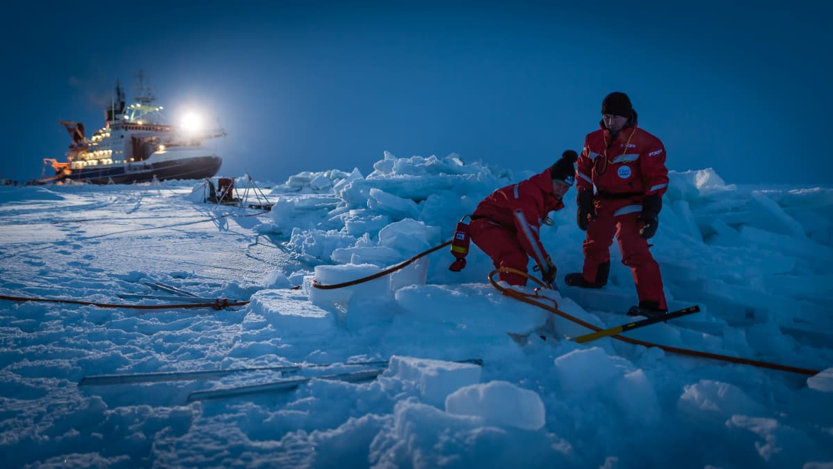 Kaksi ihmistä laskee kaapelia jäävalliin. Taustalla Polarstern-aluksen kirkkaat valot.
