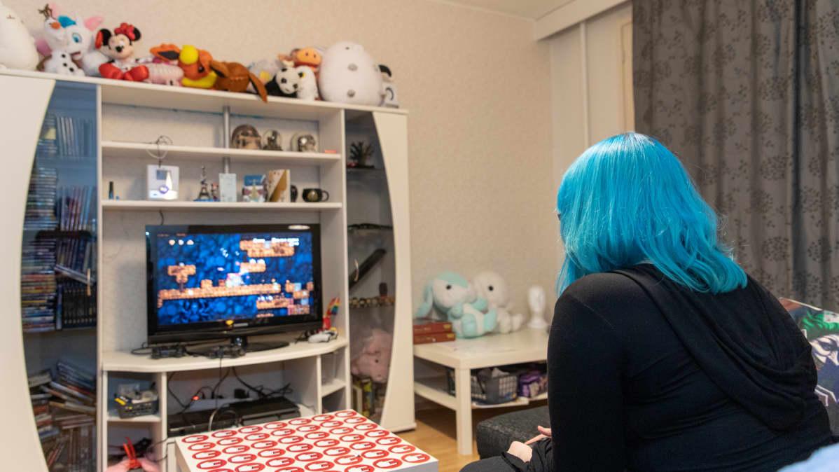 hlö pelaa play station peliä olohuoneessa kotonaan