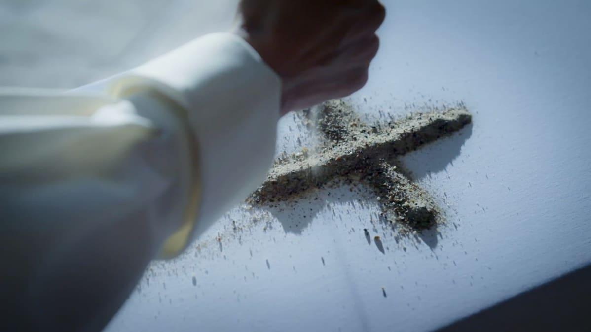 Pappi tekee kädelle hiekkaristin arkun päälle.