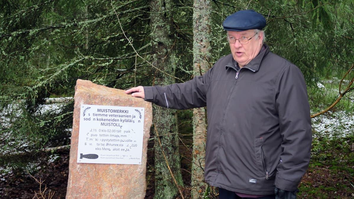 Martti Pura seisomassa muistomerkin vierellä