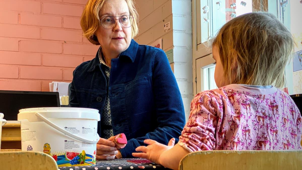 Varhaiskasvatuksen psykologi Nina Sassali askartelemassa lasten kanssa oululaisessa päiväkodissa.