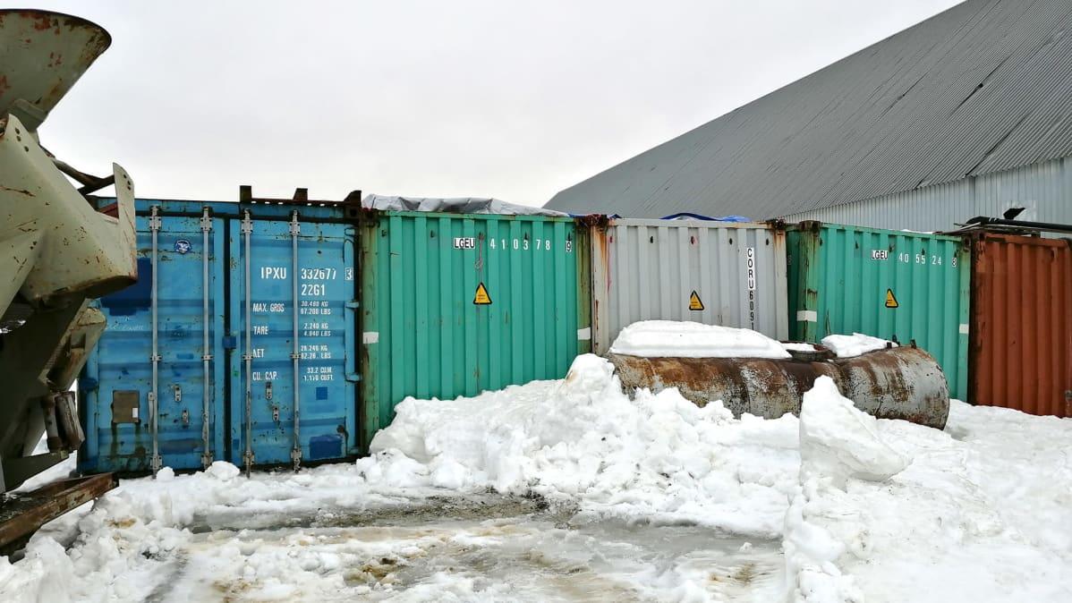 Eri värisiä kontteja vierekkäin lumessa.