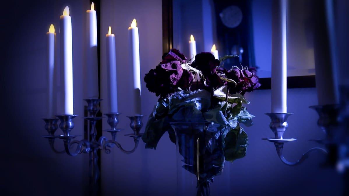 Kimppu punaisia ruusuja on kuihtunut maljakkoon. Ympärillä monta isoa metallista kynttelikköä, joissa palaa kynttilät.
