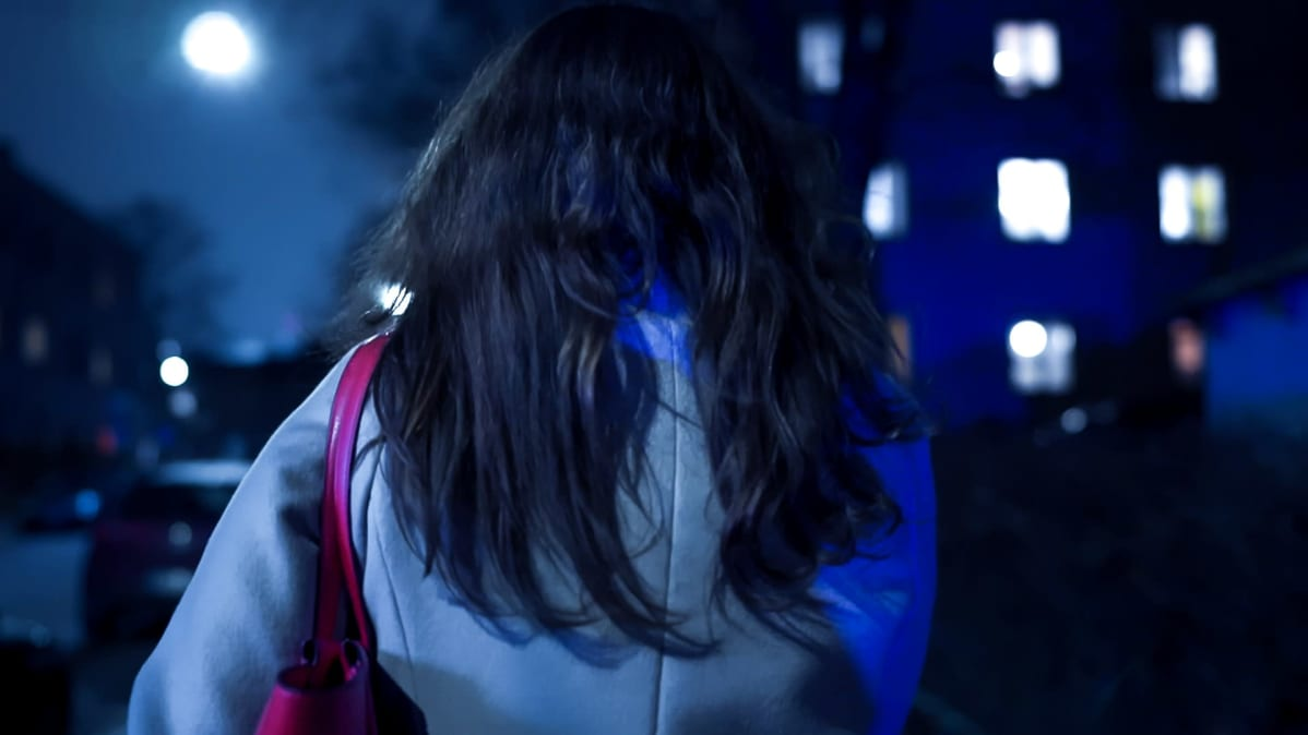 Tummatukkainen nainen takaapäin lähikuvassa. Taustalla vilkkuu poliisiauton valot.