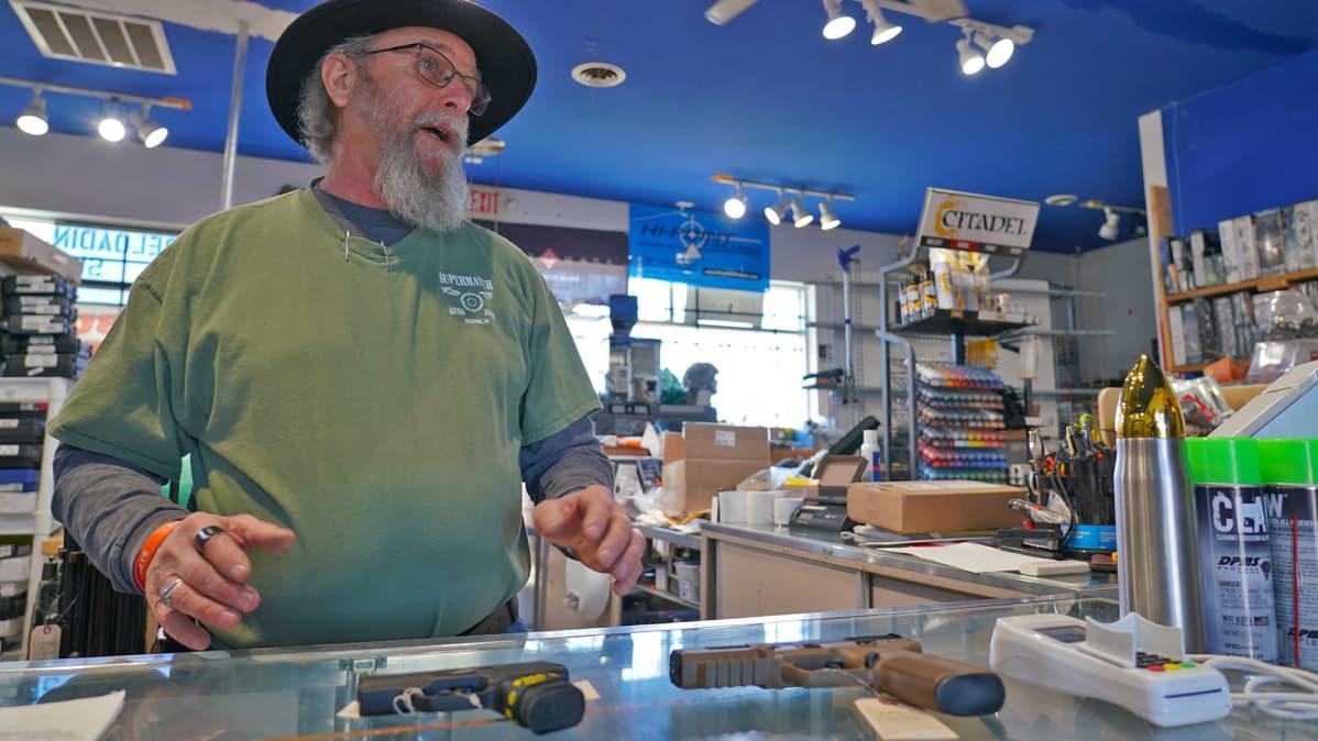 Gerald Barber esittelee suosituimpia käsiaseita asekaupassa Monroessa Michiganissa