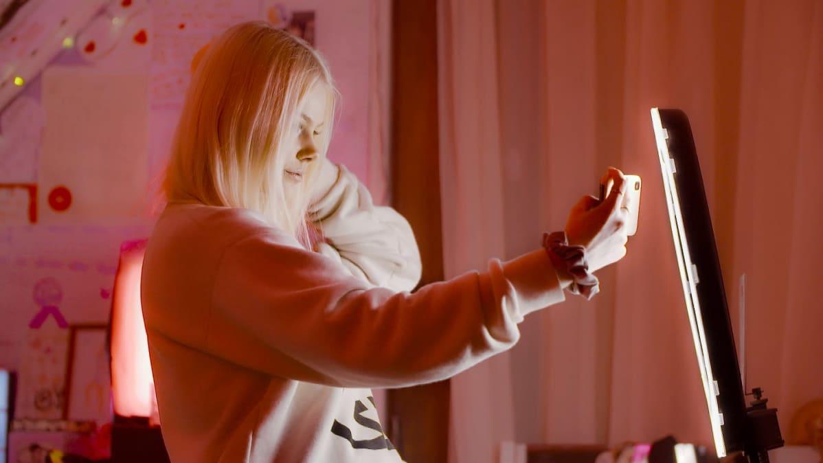 Jennifer Käld kuvaa TikTok-videota huoneessaan kuvausvalon edessä.