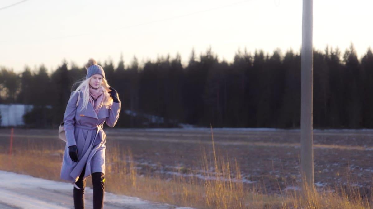 Jennifer Käld kävelee pellon laidalla.