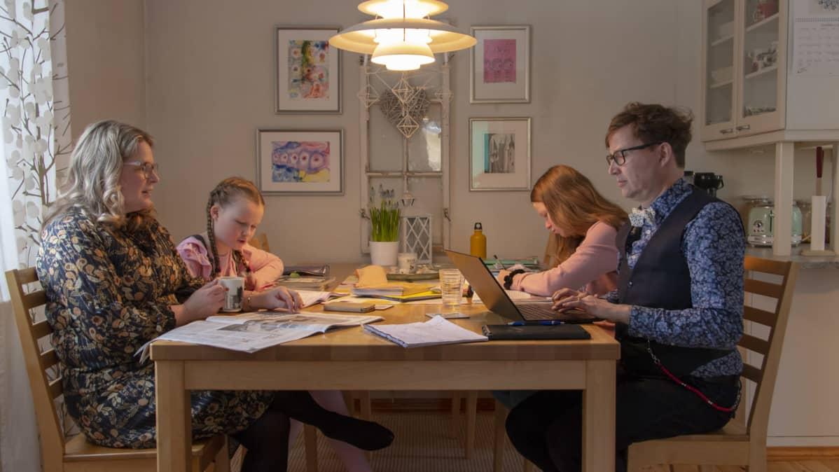 pereh auttaa lapsiaan koulutehtävissä kotona pöydän ääressä