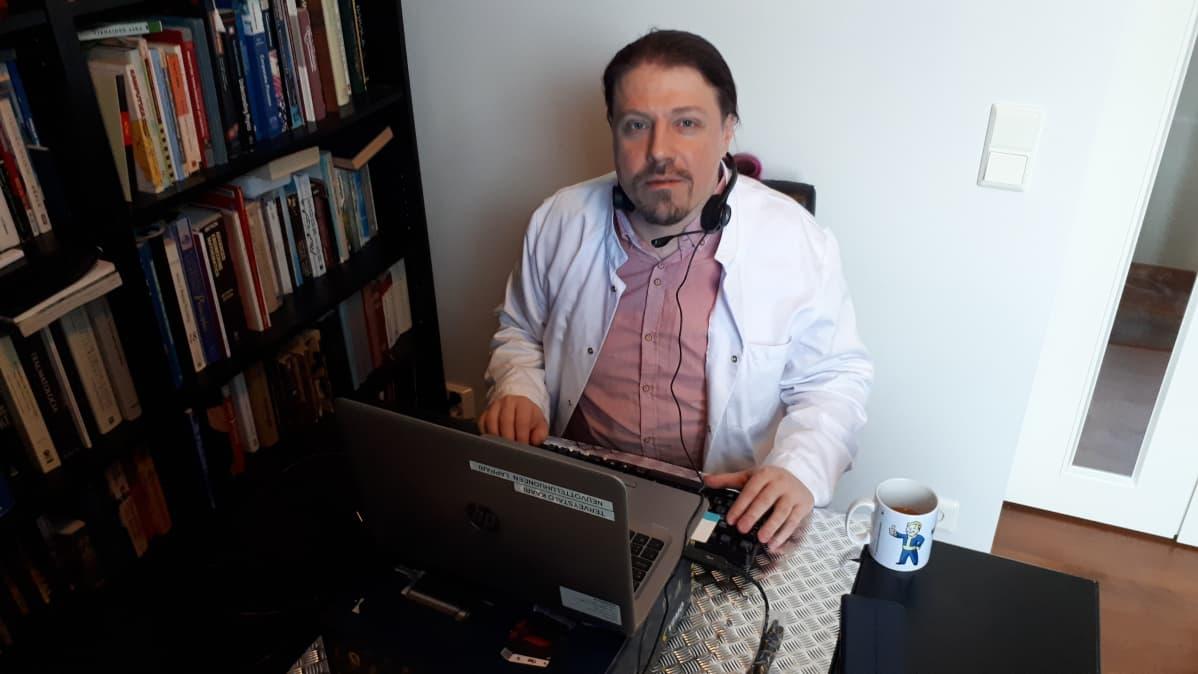 Lääkäri Jan Parkki istuu tietokoneen äärellä.