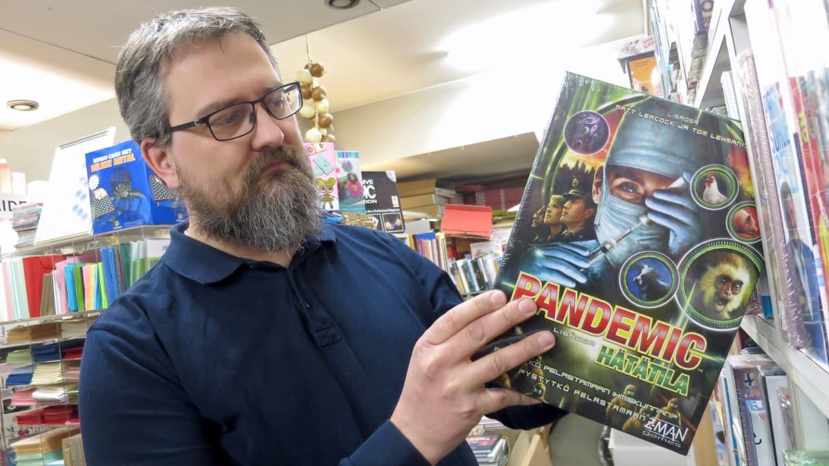 Mies ottaa kirjakaupassa lautapelin hyllystä jossa lukee Pandemic