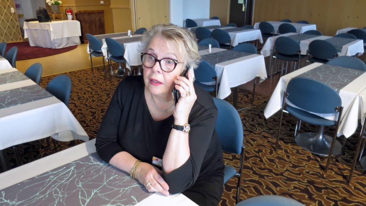 Naistarjoilija yksin tyhjässä ravintolasalissa soittaa kännykällä