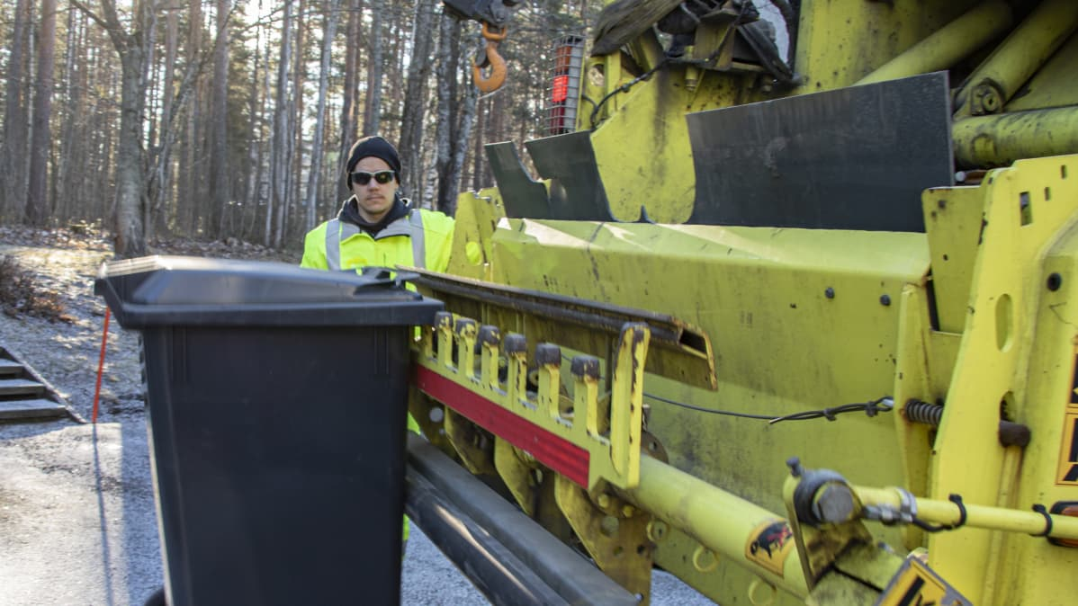 Janne Katila tyhjentämässä jäteastiaa.