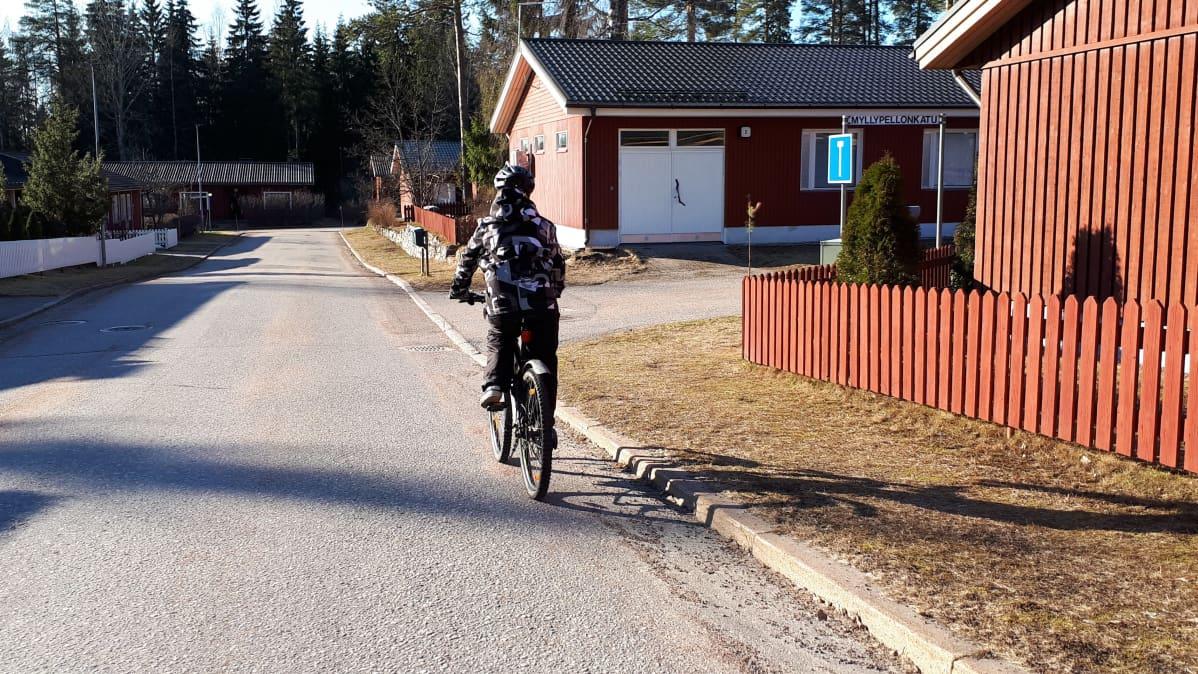 Polkupyöräilijä ajoradan oikeassa reunassa.