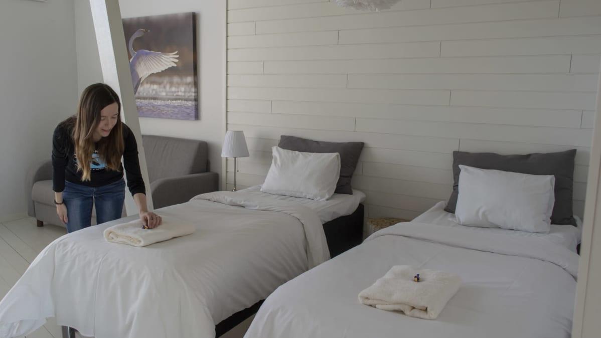 Sari Peltoniemi asettelee karkkia sängylle Liminganlahden luontokeskuksen hottellihuoneessa