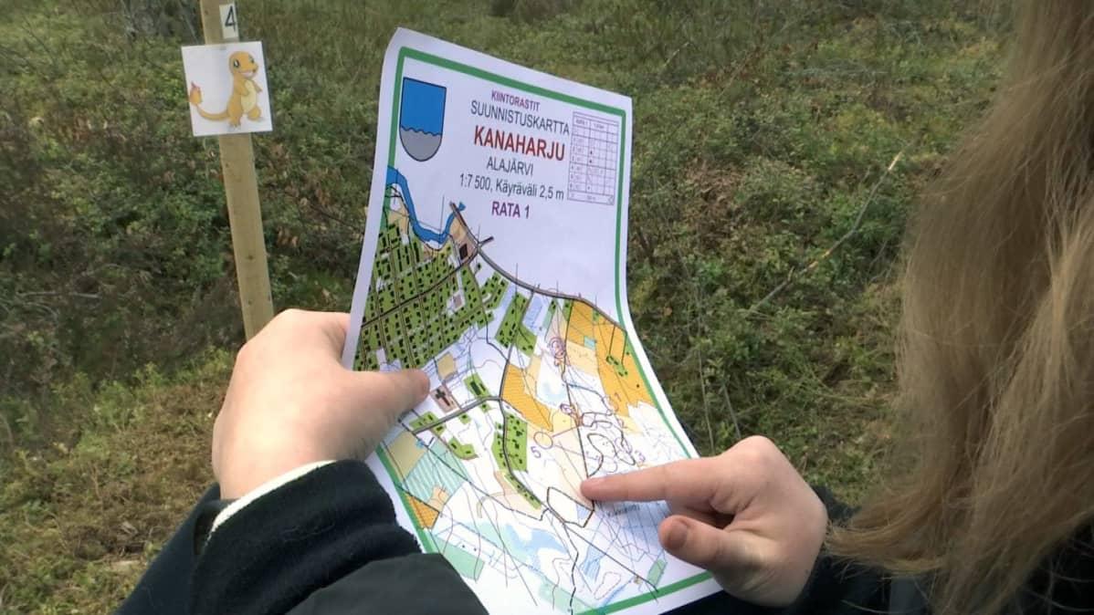 Tyttö katsoo karttaa Alajärven Pokemon-suunnistusradalla
