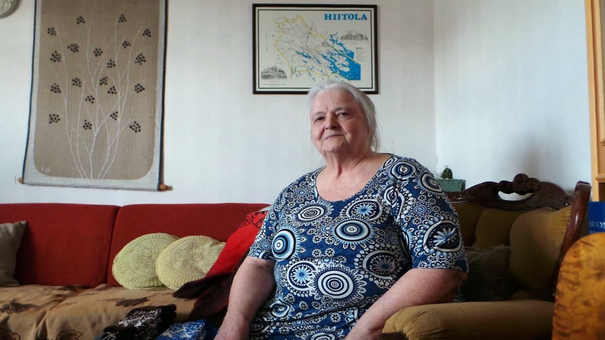 Marja-Liisa Isoviita istuu nojatuolilla ja hymyilee