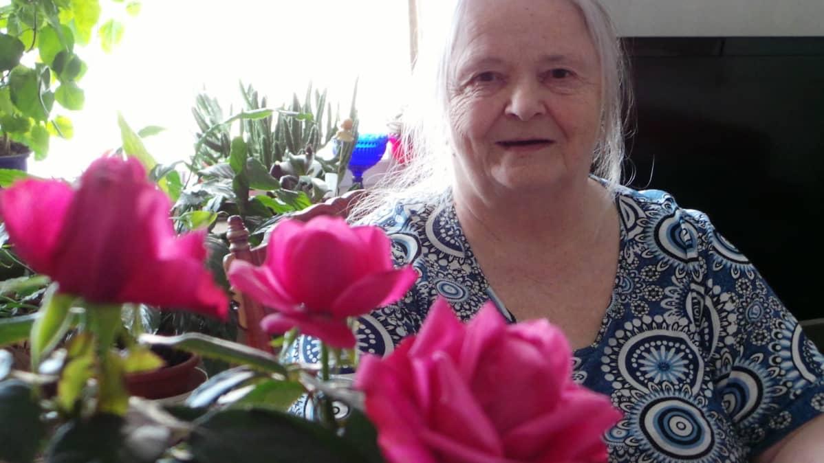 Marja-Liisa Isoviita hymyilee ruusujen takana.