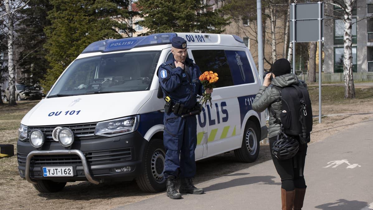 Nainen kuvaa kukkakimppu sylissä autoa vasten poseeraavaa poliisimiestä.