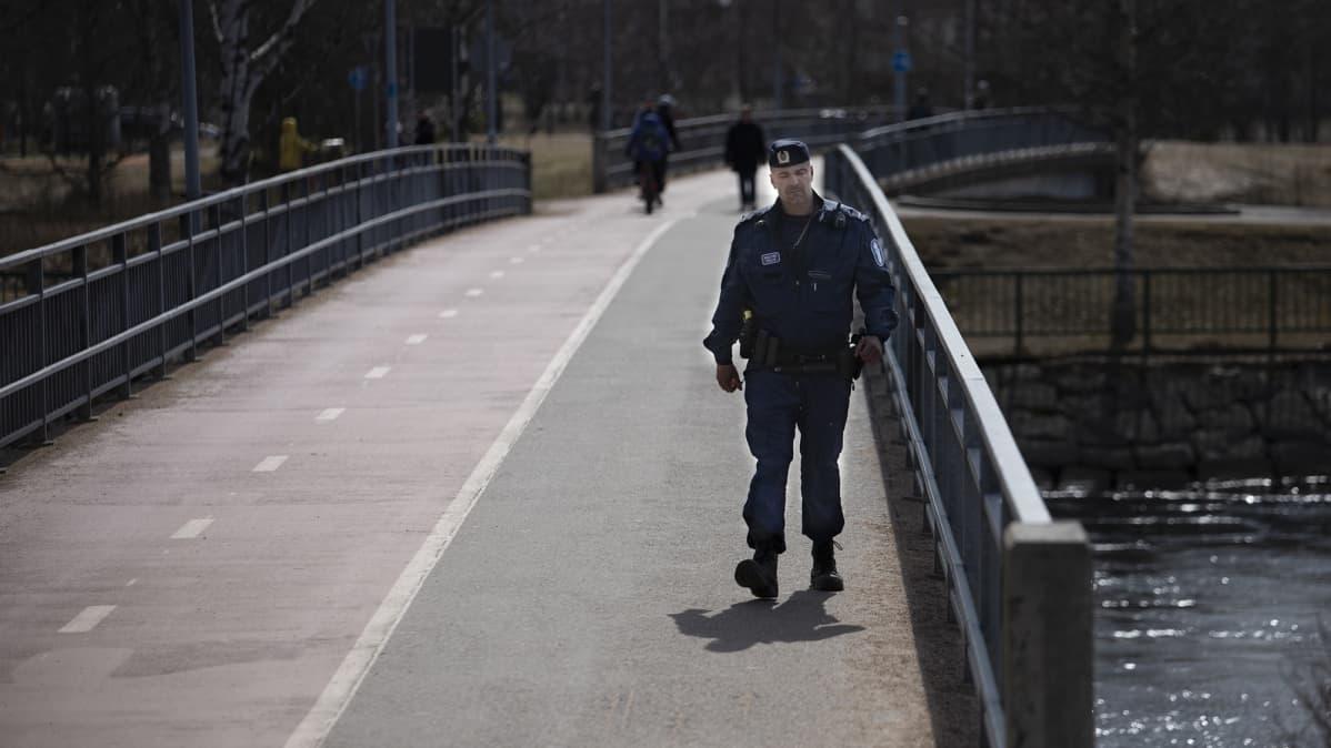 Poliisimies kävelee sillalla