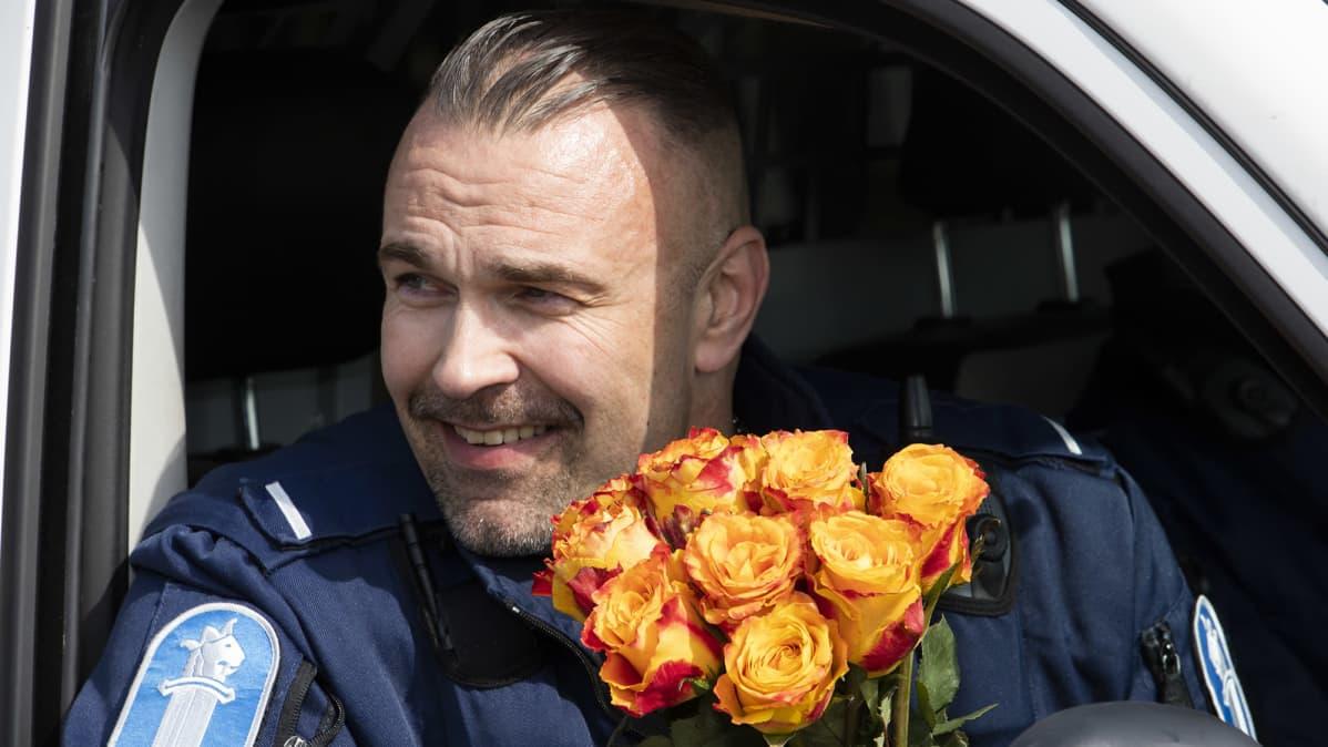 Poliisimies istuu partioautossa kimppu keltaisia ruusuja sylissään
